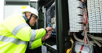 Openreach engineer working on high speed fibre broadband in street cabinet