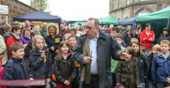 Picture of First Minister Alex Salmond, with children behind him, cutting the ribbon to open the new Turra Market
