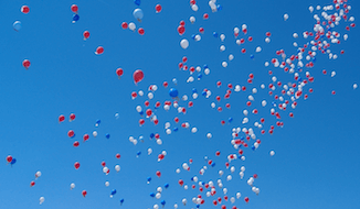 Balloon release. Red White and Blue balloons floating in a cloudless blue sky