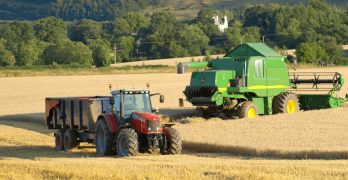 Tractor, trailer and combine harvester in a field