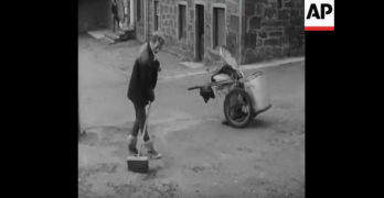 Still from AP film of a litter dropper starting his community service sweeping the street of Turriff