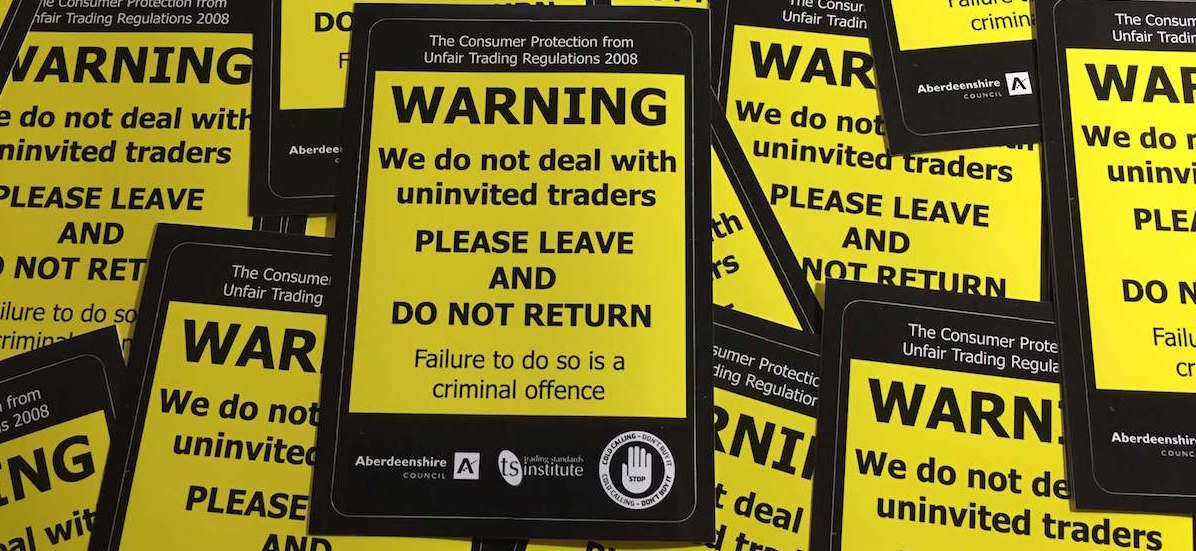 Yellow and black warning sticker warning door step traders not to call.
