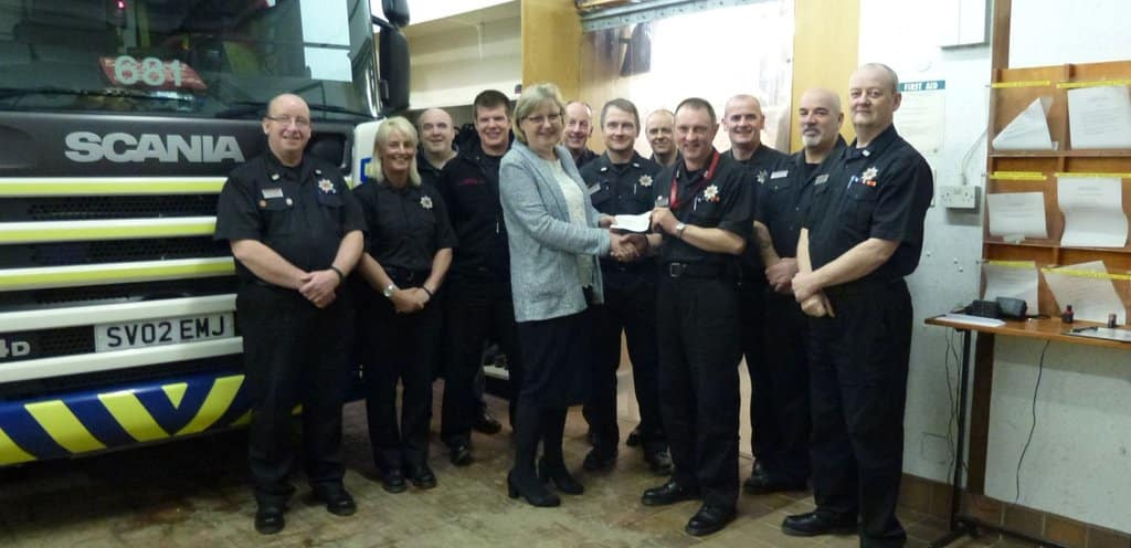 ACE Winches Marketing Director Hayley Yule hands cheque donation to Turriff Fire Station's Mike Bremner