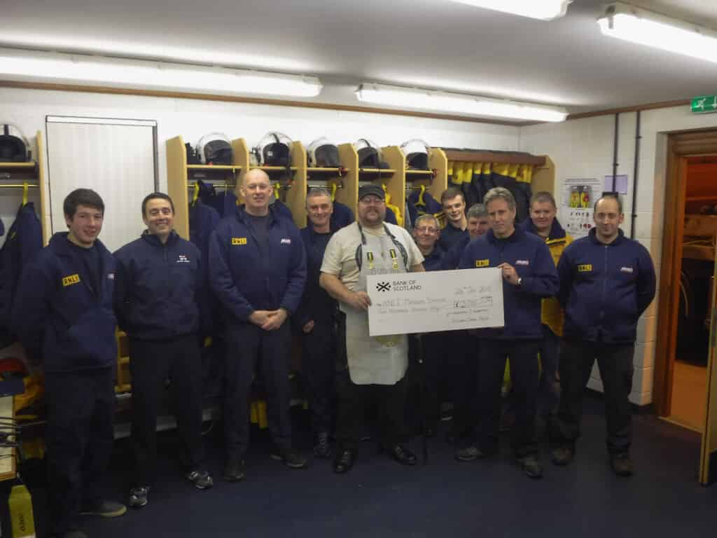 Calum Mackinnon from Ye Corporation Of Squaremen with members of RNLI Macduff lifeboat crew