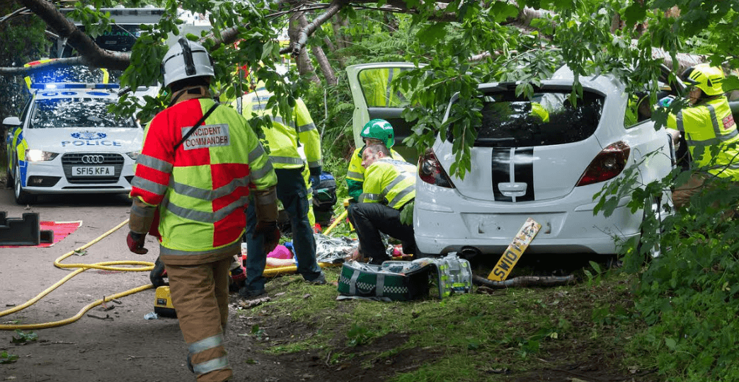 A still from the new Safe Drive Stay Alive film showing a crashed white car with emergency services working on it