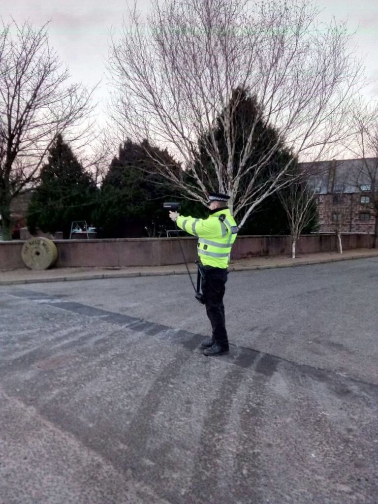 Police Scotland officer with a speed gun outside the Old Mill in Turriff