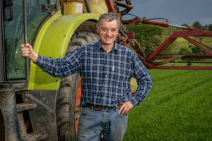 NFUS Vice President Charlie Adam standing in a field next to a green tractor