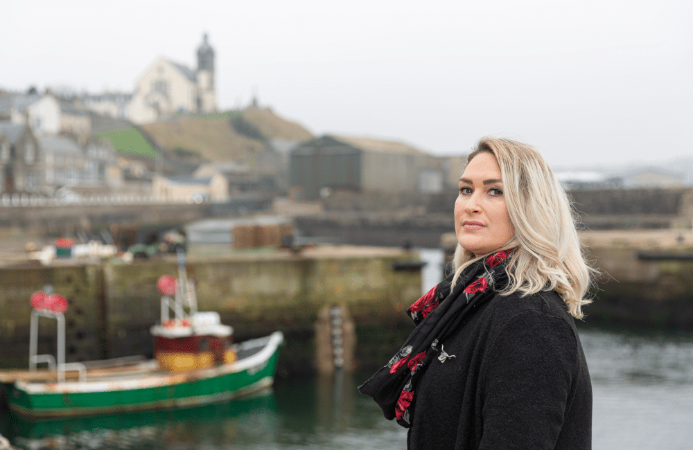 Profile picture of Karen Adam at Macduff harbour with boats and Macduff kirk in the background